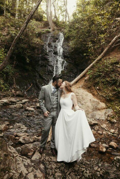 Pareja de esposos besándose en un bosque con una mini cascada entre las rocas detrás, él vistiendo un traje gris con corbata plateada y ella un vestido blanco de tirantes grueso largo hasta el piso con una media coleta