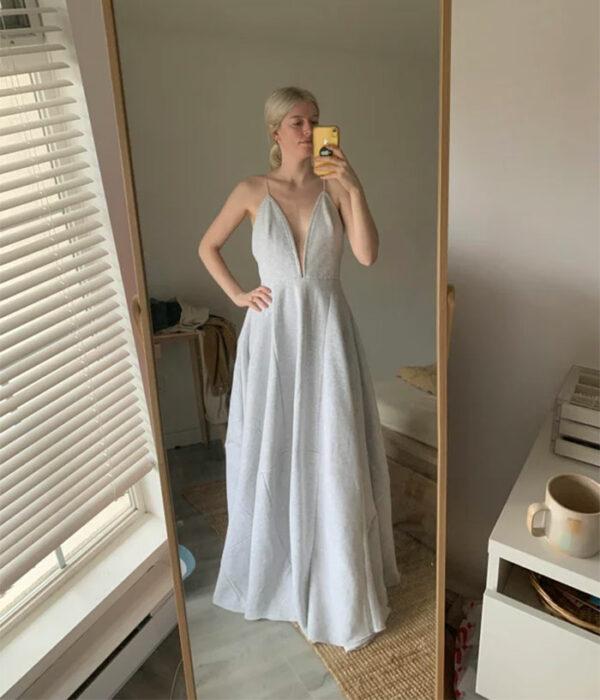 Mujer rubia con coleta baja tomándose selfie frente al espejo con vestido largo de tirantes hecho con pants grises