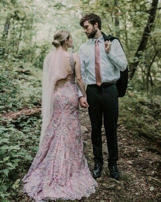 Pareja de esposos posando en el bosque, él de frente con blusa blanca, corbata rosa, pantalón negro y el saco sobre el hombro y ella con recogido bajo, velo rosa y vestido rosa corte sirena con escaje