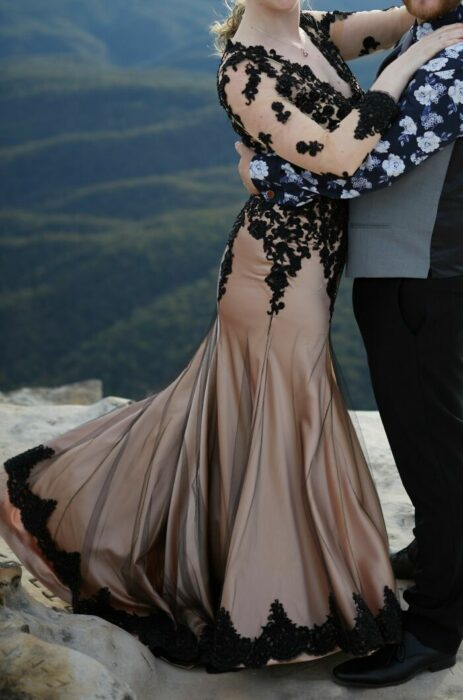 Pareja de esposos abrazándose, él con pantalón y zapatos negros y chaleco gris y ella con vestido en corte sirena color dorado con una capa transparente de encaje negro