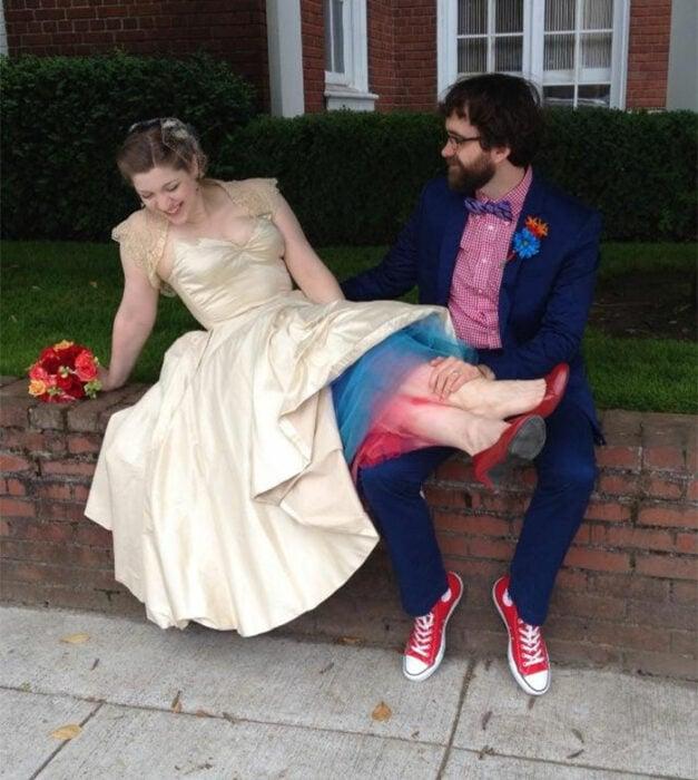 Pareja de esposos sentados en una bardita de ladrillos rojos. Él vistiendo un traje azul marino, camisa roja de cuadros blancos y converse rojos. Ella con vestido color perla con fondo azul y rojo y zapatos rojos con ramo de flores en color naranjas y rojo