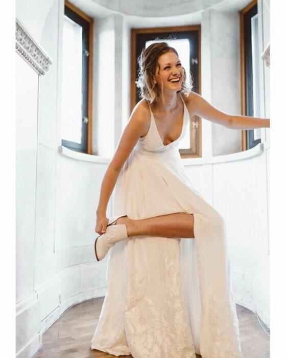 Novia de cabello corto riendo mientras usa vestido largo blanco y sube su pierna para cerrar su botín blanco mientras se apoya de la pared con su mano izquierda