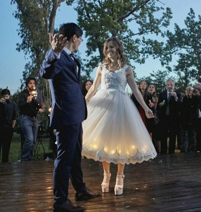 Pareja de novios baila en la pista con los invitados viéndolos al rededor; él con traje azul marino y ella con vestido de encaje hasta el tobillo con luces en la falda