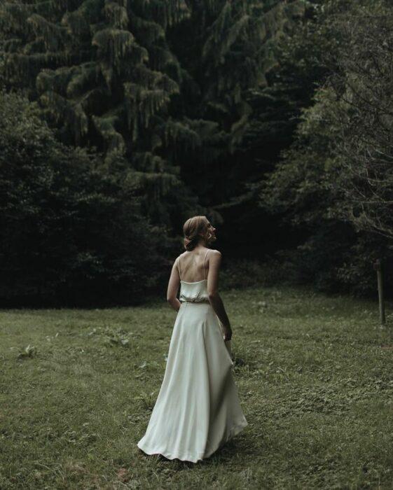 Novia de espaldas caminando por el bosque con un vestido de seda blanco hasta el piso de tirantes con un recogido bajo