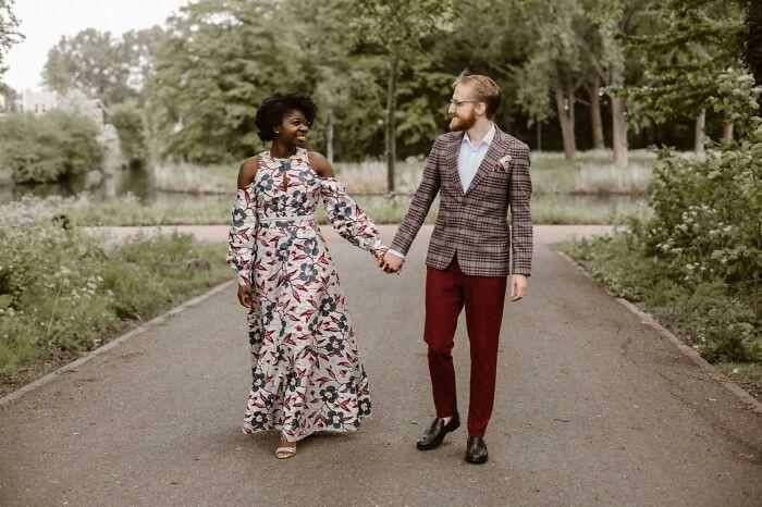Pareja de esposos caminado de la mano por una carretera en el bosque, ella con un vestido de novia largo, blanco con flores azules y ramas rojos con mangas largas y hombros descubiertos y él con un saco café con cuadros rojos, camisa blanca y pantalón guinfa