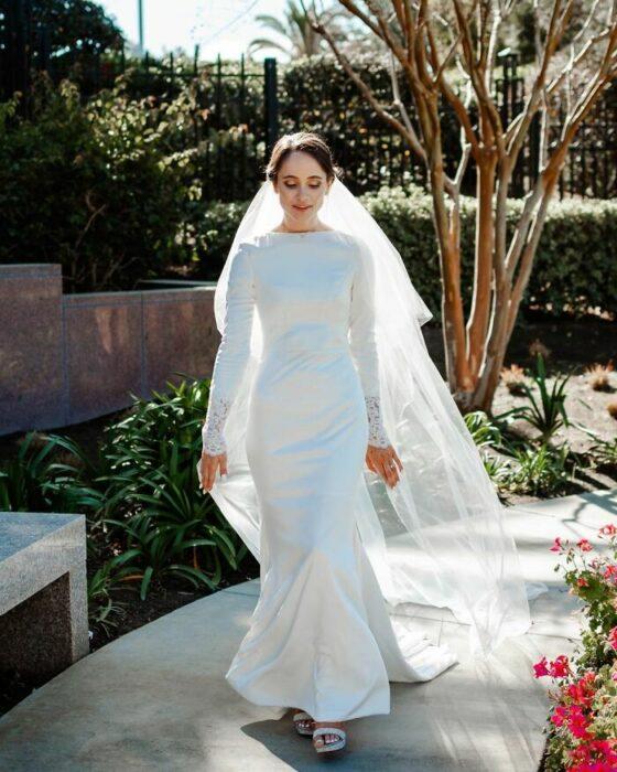 Novia caminando por un camino de concreto en un jardín con vestido largo de margas largas, sandalias altas y un largo velo que llega hasta el piso