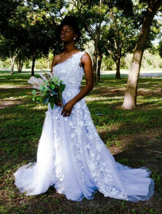 Mujer negra posando en un parque con un vestido de novia blanco, detalles de flores en 3D con solo un tirante grueso de lado izquierdo y un ramo de plantas verdes