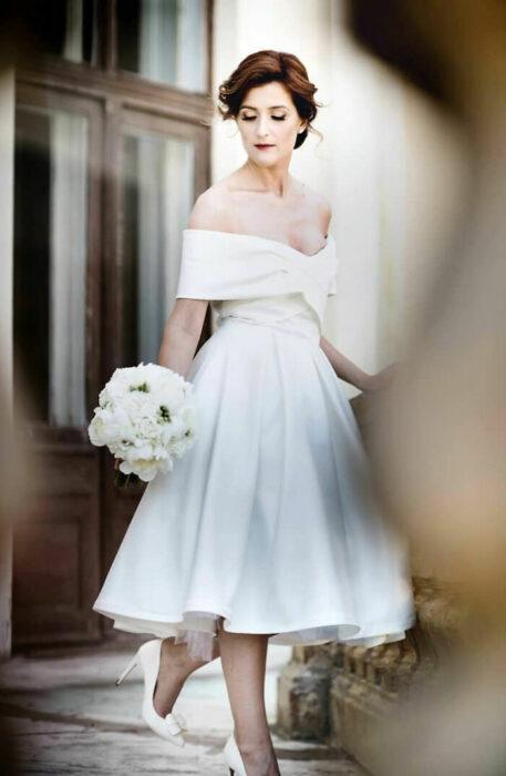 Mujer castaña con recogido bajo con vestido de novia estilo pin-up abajo de la rodilla con zapatos de tacón y ramo blanco