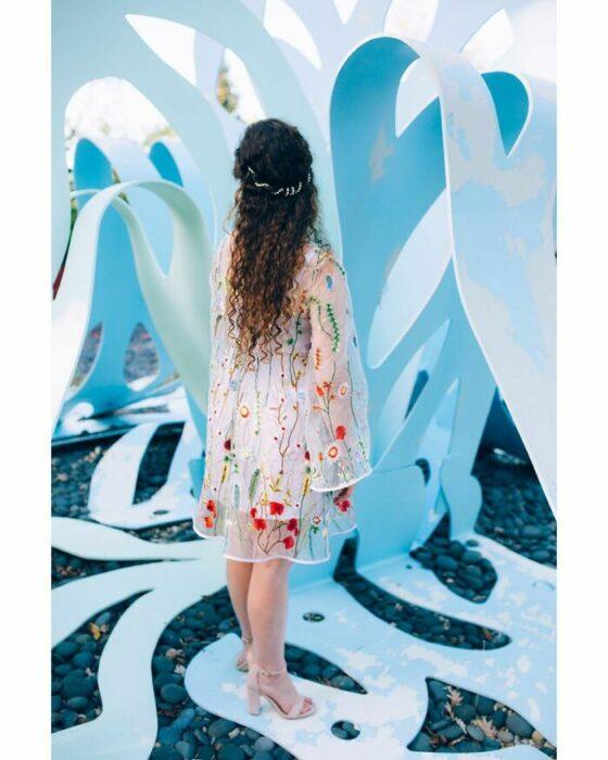 Novia con cabello rizado largo de espalda mirando hacia arriba con un vestido blanco hasta las rodillas con una capa de transparencia con flores de colores y sandalias beige de tacón