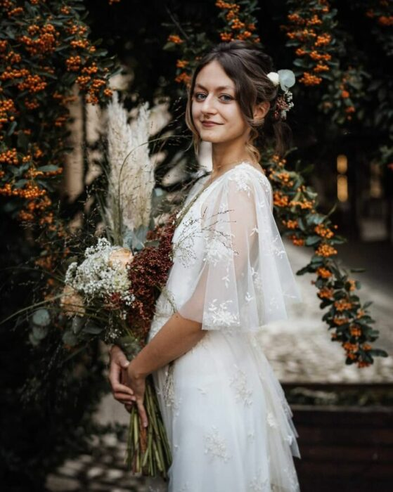 Mujer castaña con recogido de novia despeinado con vestido estilo bohemio con mangas transparente y un ramo de flores en color guinda, blanco y naranja