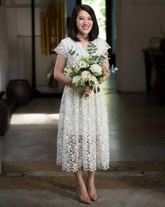 Novia de melena corta negra con vestido de encaje arriba de los talones, zapatos nude y un ramo de flores blancas con hojas verdes