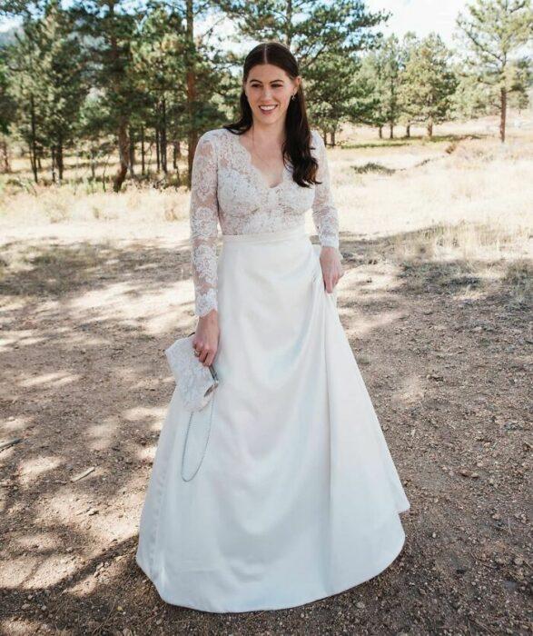 Novia con media coleta usando un vestido con la parte superior de encaje con escote en V y la falda de satín larga