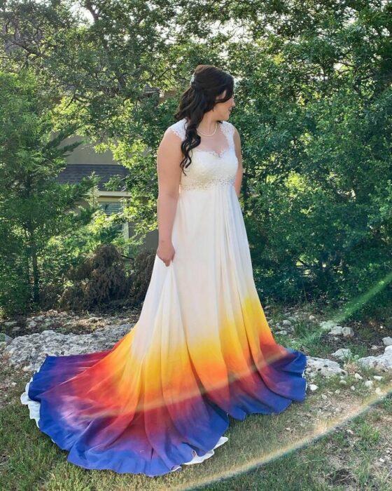 Novia con peinado de media coleta rizada con vestido largo con escote en corazón y mangas de tirantes y la parte inferior con un degrado de colores