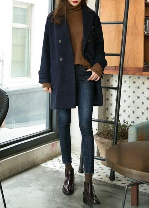 Outfit para la oficina de otoño-invierno de abrigo color azul marino, suéter color camel, jeans y botines negros