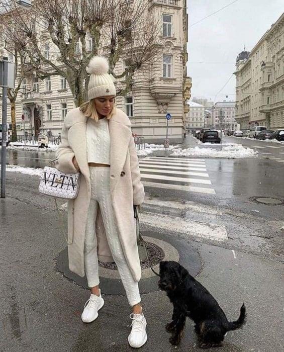 Chica usando un total white look de tenis, leggings y crop top tejidos, con abrigo y gorrito con motita