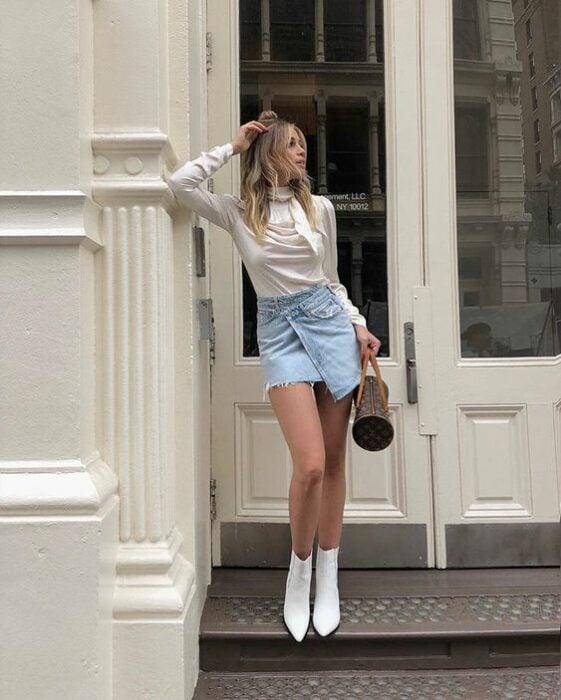 Chica usando botines blancos, con mini falda denim, con blusa blanca de manga larga y bolso color café