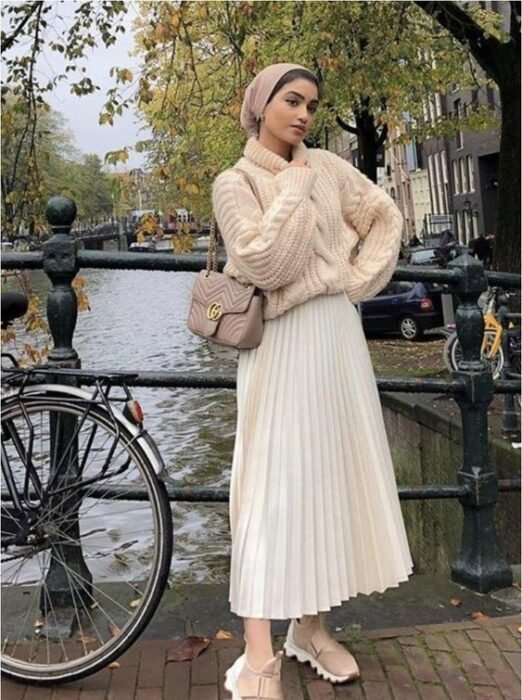 Girl wearing a total white tennis look, maxi skirt, high neck sweater and puff sleeves