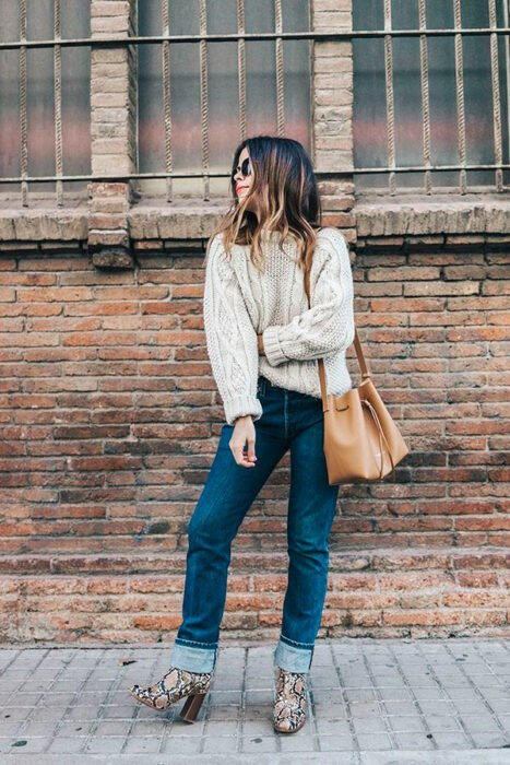 Girl wearing python boots with beige sweater jeans and khaki bag