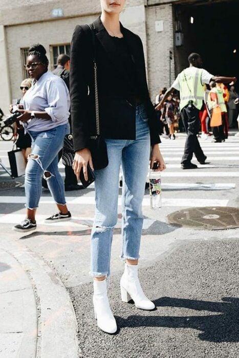 Chica usando botines blancos y jeans denim, con saco y blusa negra con bolsa de mano del mismo color