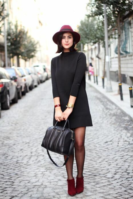 Chica usando sombrero de color guinda con outfit de botines color guinda, medias negras y un little black dress