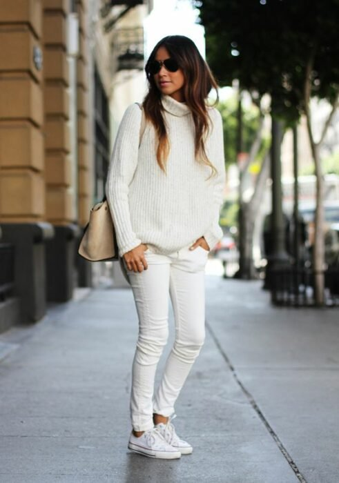 Girl wearing a total white tennis look, skinny jeans, long sleeve sweater and high neck