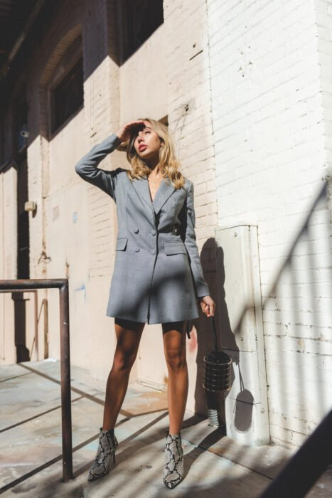 Girl wearing python boots with gray blazer as dress