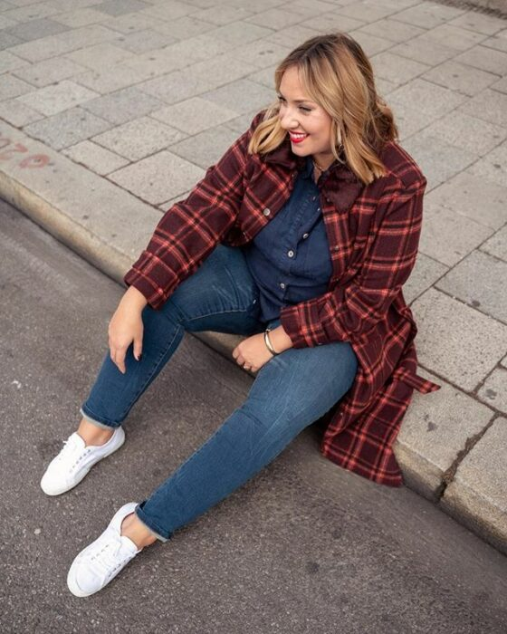 Curvy girl wearing jeans and denim blouse, white tennis shoes and plaid brick coat