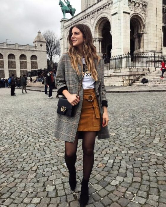 Outfit for the autumn-winter office of gray coat, white blouse, camel mini skirt and black tights and ankle boots