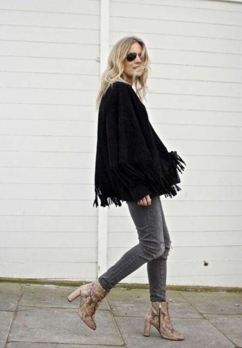 Chica usando botas pitón con jeans negros deslavados y suéter holgado negro con gafas de sol