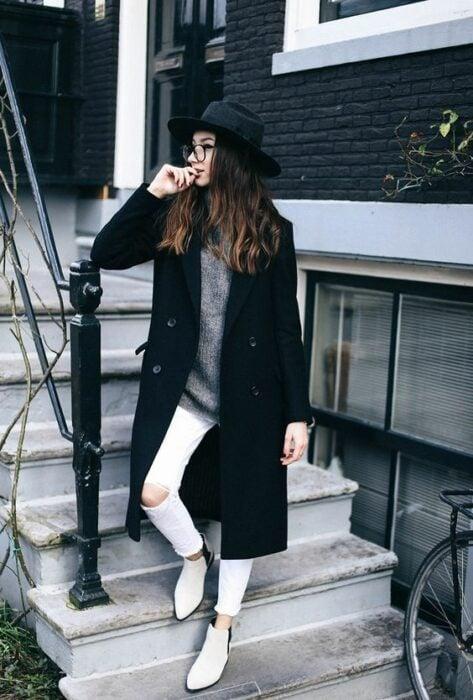 Chica usando botines blancos y jeans rasgados blancos, blusa gris con abrigo largo y sombrero negros