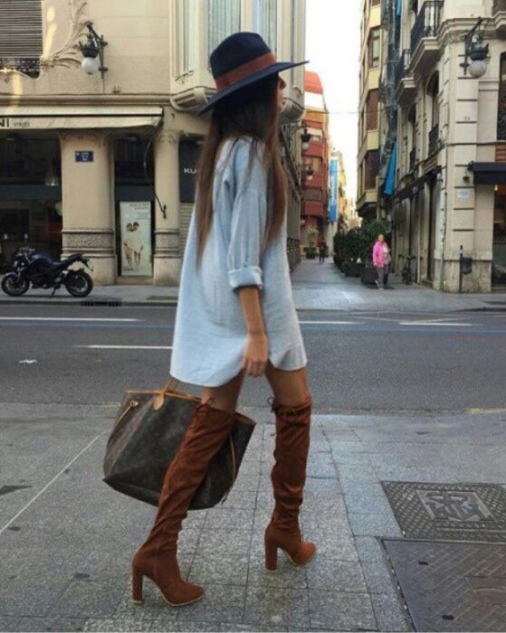 Chica usando sombrero de color negro con outfit de botas altas camel, vestido denim tipo camisa, bolso de mano color café