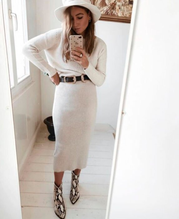 Girl wearing a total white look of midi skirt, boots, long sleeve blouse and hat