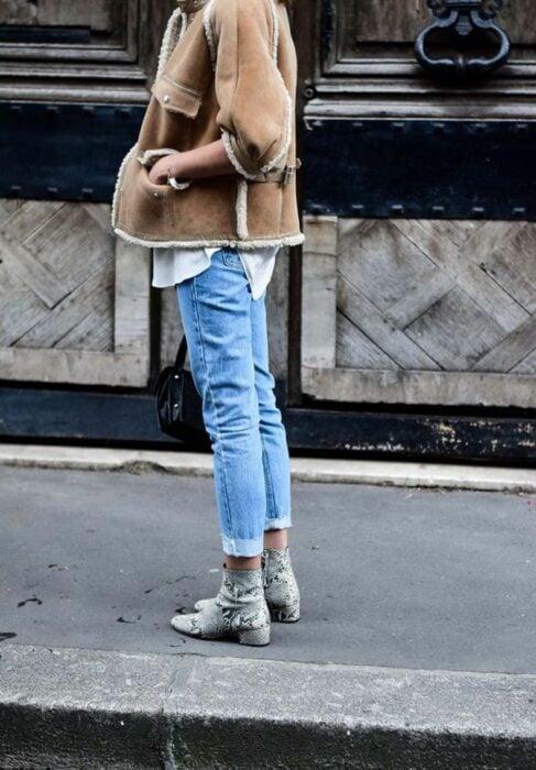 Chica usando botas pitón con jeans, camisa y chaqueta de color caki