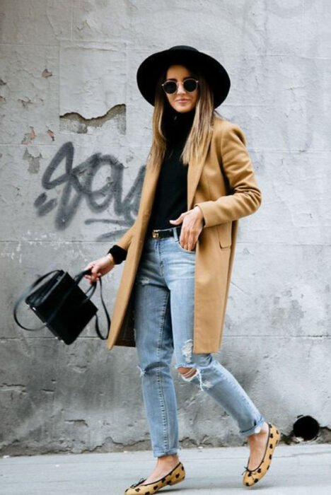 Girl wearing black hat with skirt outfit, ripped jeans, black blouse and camel trench coat