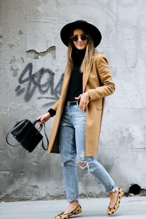 Chica usando sombrero de color negro con outfit de falts, jeans rasgados, blusa negra y gabardina color camel