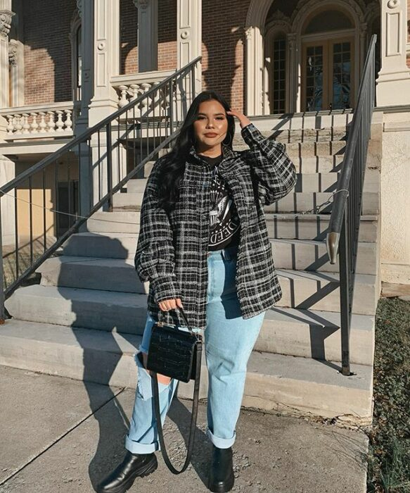 Curvy girl wearing black ankle boots, blue mom jeans, gray blouse and gray plaid coat, with black handbag