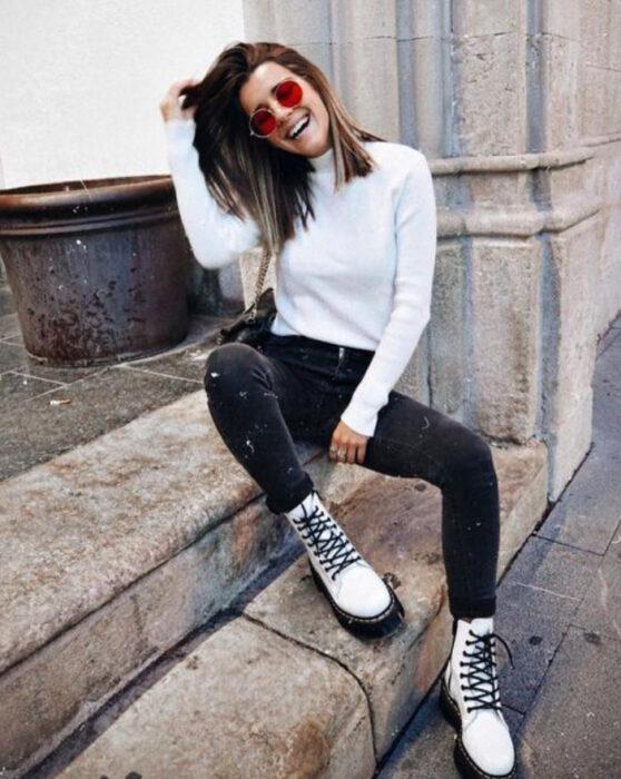 Chica usando botines blancos y jeans negros, con blusa de manga larga blanca y lentes de sol de cristal rojo