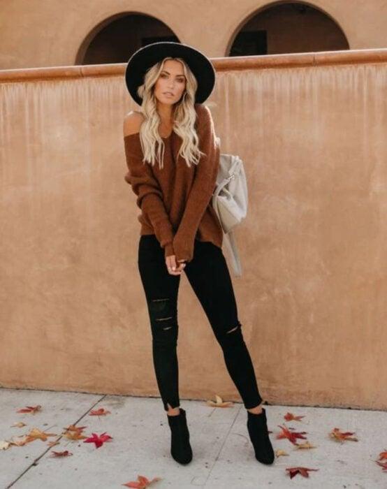 Chica usando sombrero de color negro con outfit de jeans y botines negros, suéter con escote de ojal color camel y bolso de mano blanco