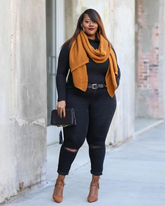 Curvy girl wearing black jeans and sweater, with mustard scarf and heels of the same color