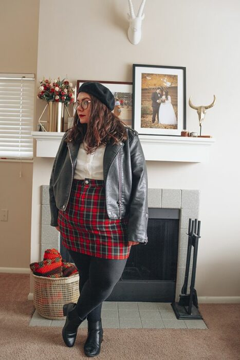 Curvy girl wearing ankle boots and black leggings, red plaid skirt, white blouse and gray jacket and a black beret