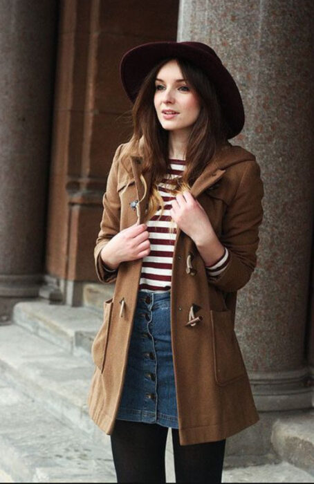 Girl wearing black hat with outfit of black stockings, denim mini skirt, striped blouse and caki coat