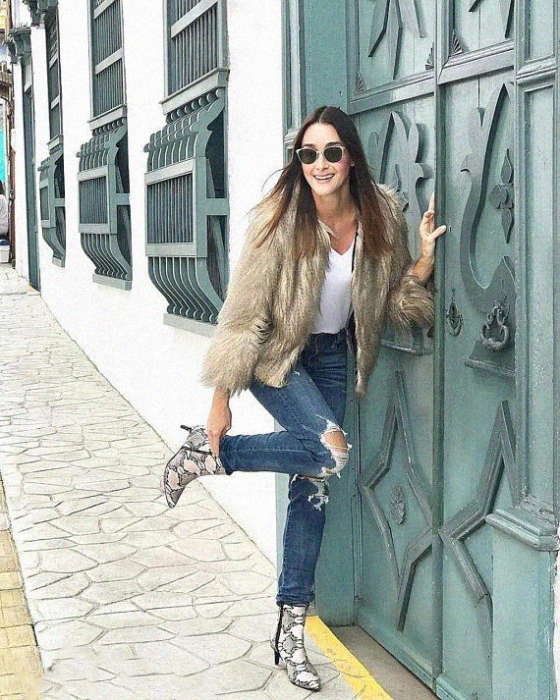 Girl wearing python boots with ripped jeans, white blouse and furry jacket