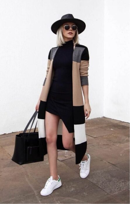 Outfit for the autumn-winter office of striped sweater, short black dress, white tennis shoes, hat and black bag