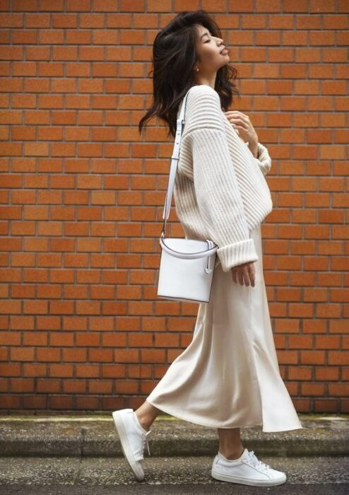 Girl wearing a total white tennis look, long skirt and baggy sweater