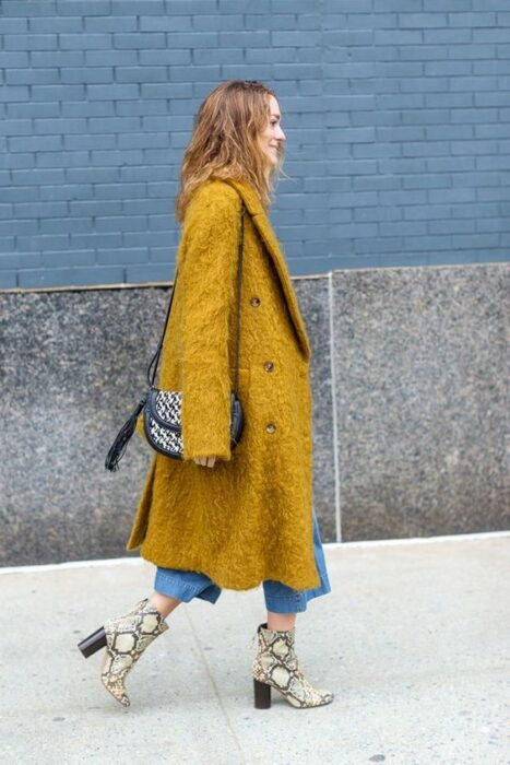 Girl wearing python boots with jeans and long mustard coat