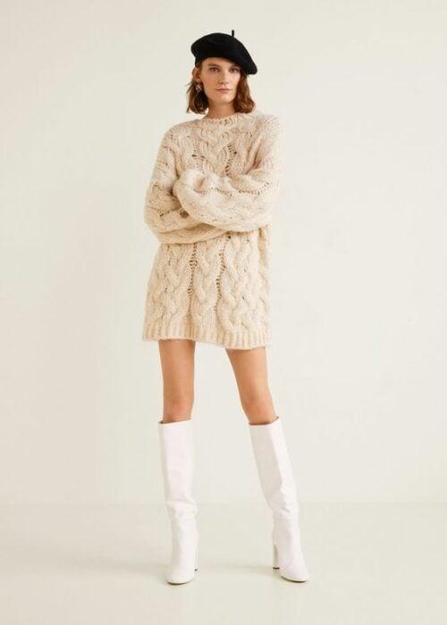 Chica usando botas blancas y vestido de jersey color beige