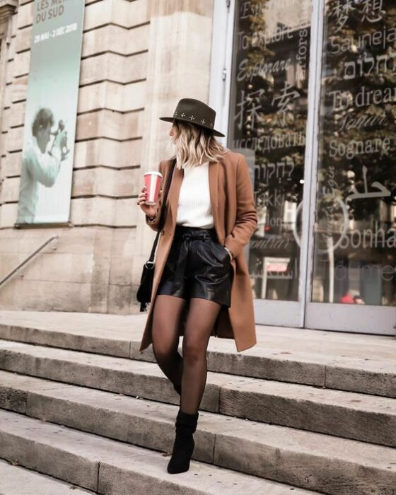 Outfit for the autumn-winter office with camel coat, white sweater, black shorts, black stockings and ankle boots, as well as a black hat
