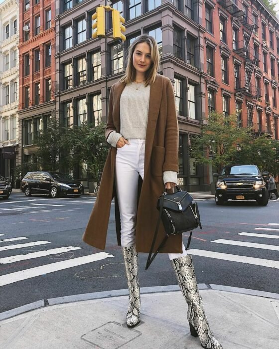 Girl wearing python boots with white jeans, beige sweater and long brown coat, with black handbag