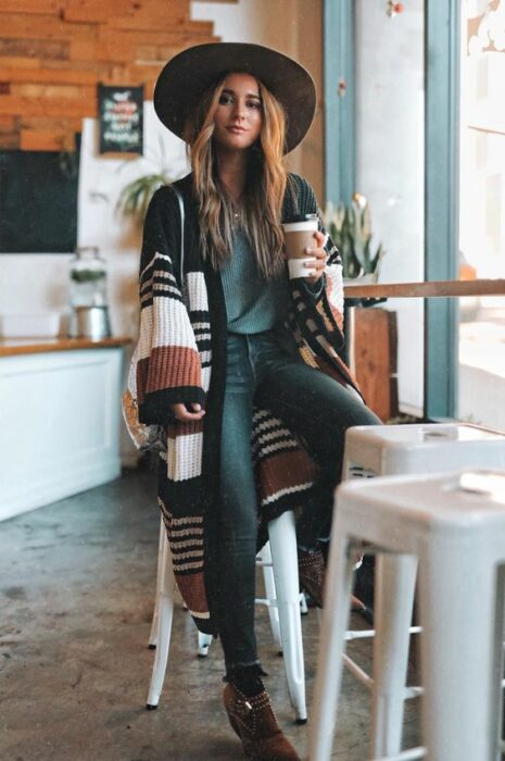 Girl wearing black hat with jeans outfit, petrol blue blouse and long striped cardigan of different colors