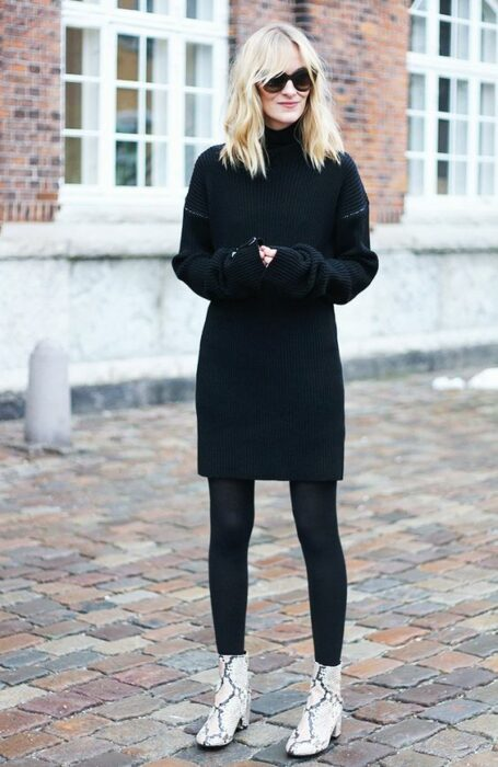 Girl wearing python boots with black leggings, somewhat baggy black sweater and sunglasses